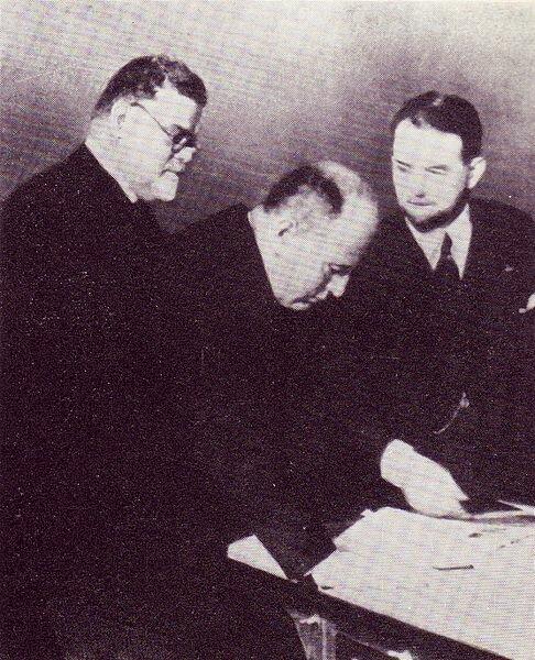 Министр образования Италии профессор Джованни Джентиле (слева) и Бенито Муссолини (в центре) изучают предпечатные материалы тома Итальянской энциклопедии