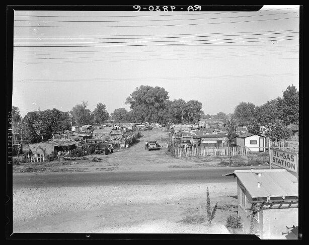 Лагерь мигрантов близ Скараменто, Калифорния. 80 семей самостоятельно построили дома, при условии арендной платы на землю в размере 1,25 долл. в месяц, куда входила и питьевая вода. Фотограф Д. Ланж, ноябрь 1936 г.