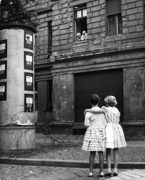 Девушки из Западной Германии разговаривают с дедом и бабкой из Восточной, рядом с первым вариантом Берлинской стены